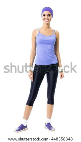 Full body portrait of smiling sporty brunette woman in violet sportswear, isolated against white background. Young female fitness instructor or personal trainer at studio shot.