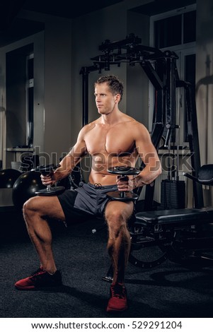 Full body portrait of sporty shirtless male holds dumbbells in a gym club.