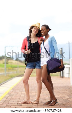 Full body portrait of two young women standing at railroad station - stock photo