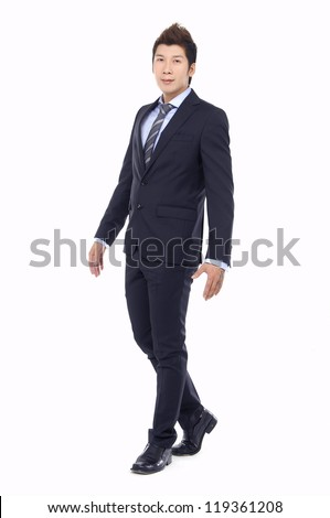 Full body portrait of walking young business man