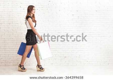 full body portrait of woman in black and white dress walking while carrying shopping bags - stock photo
