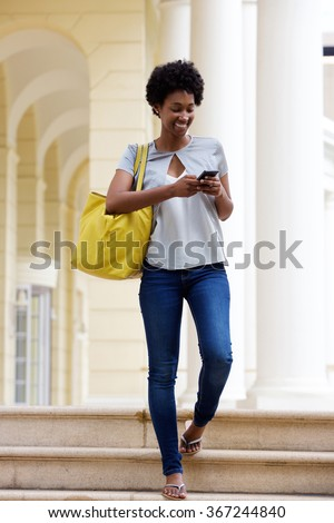 Full body portrait of young african woman coming down the steps of a building and sending text message from her mobile phone - stock photo