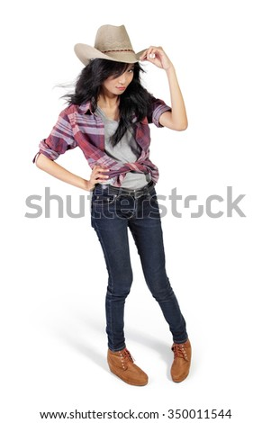 Full body portrait of young attractive woman dressed in cowgirl style standing pose, isolated on white background