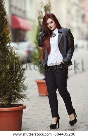Full body portrait of young beautiful lady wearing stylish classic clothes walking at street of the old city. Model looking at camera. Female fashion concept. Toned  - stock photo