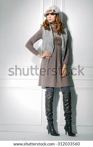 Full body portrait of young fashion model in boots posing in studio - stock photo