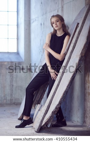 Full body portrait of young female in a black costume. - stock photo
