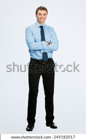 Full body portrait of young happy smiling business man, over grey background