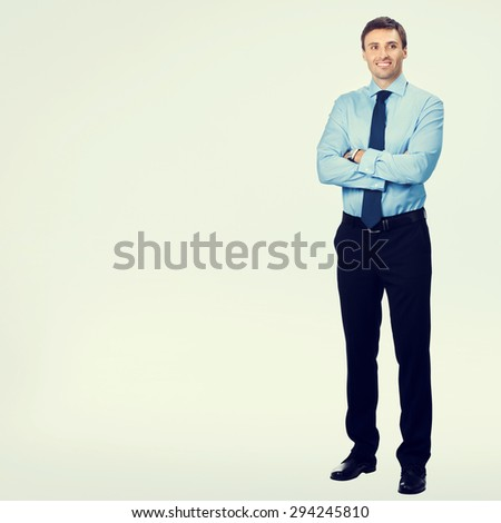 Full body portrait of young happy smiling businessman, in blue confident business wear, with blank copyspace area for slogan or text message - stock photo