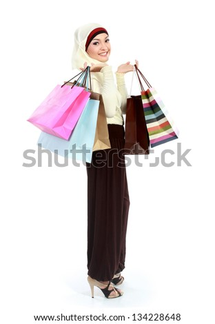 full body portrait of young muslim woman shopping carrying many shopping bags - stock photo