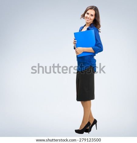 Full body portrait of young smiling businesswoman with blue folder, with blank copyspace area for slogan or text - stock photo