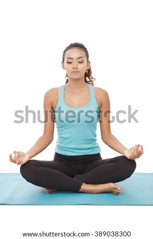 full body portrait of young woman doing yoga on the mat isolated on white background