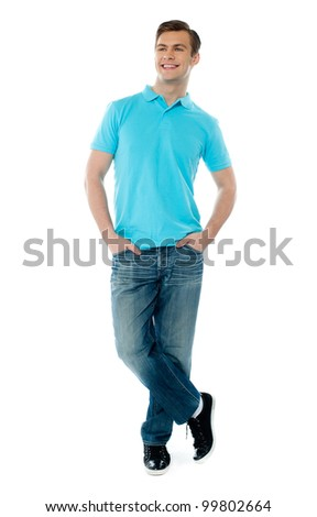 Full-body pose of smiling man posing in casuals with crossed legs