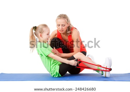 Full body shot of a little girl doing exercise with weights with an instructor on the mat . Orange, green and black colors - stock photo