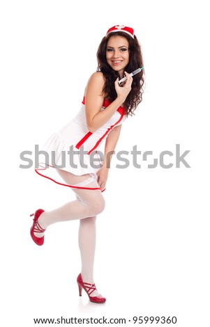 Full body shot of a sexy beautiful young nurse wearing red high heels shoes holding a syringe  and smiling on isolated white background. High resolution studio image with copy space for text. - stock photo