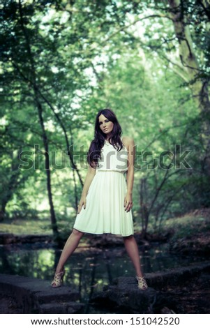 full body shot of a woman in white dress standing in the wood - stock photo