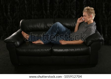 Full body shot of a young man laying on a leather sofa barefoot with his feet up talking on a mobile phone and smiling