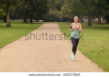 Full  Body Shot of an Athletic Woman Doing a Running Exercise at the Park with a Serious Facial Expression.