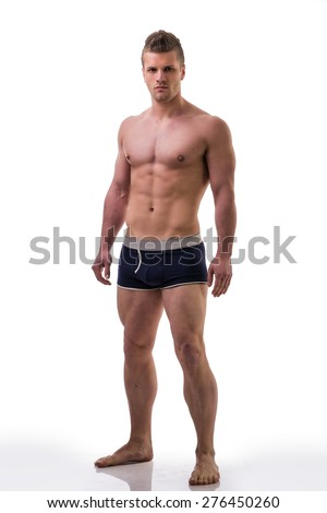 Full body shot of muscular young man standing and looking at camera smiling, shirtless, wearing underwear - stock photo