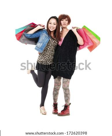 Full body shot of two beautiful asian women carrying shopping bags - stock photo