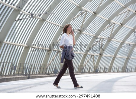 Full body side portrait of a smiling business woman walking and talking on mobile phone - stock photo