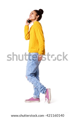 Full body side portrait of stylish young woman talking on mobile phone and walking over white background - stock photo