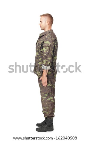 Full body side view of young army soldier standing in attention isolated on white background.