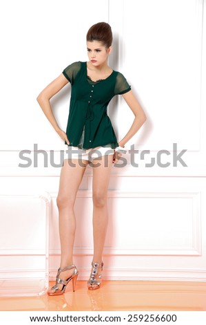 Full body standing young woman and shorts posing in studio - stock photo