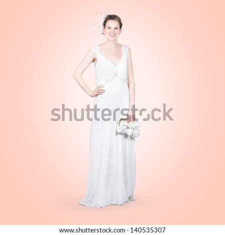 Full body studio portrait of an elegant bride holding clutch bag with matching white wedding dress and floral fascinator