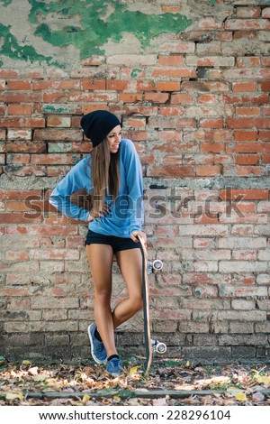 Full body teenager portrait with skateboard against brick wall.  - stock photo