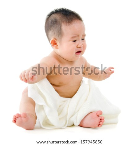 Full body unhappy Asian baby boy crying, sitting isolated on white background