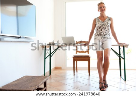 Full body view of a mature professional business woman working from home and sitting on the edge of her work desk against a sunny glass door with a plasma tv blank screen. Home and office technology. - stock photo