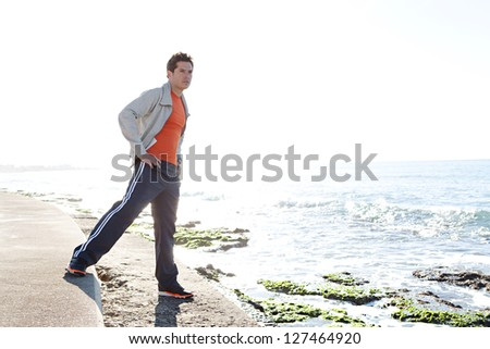 Full body view of a sports man stretching his arms after exercising by the sea, next to the water, against a blue sky background. - stock photo