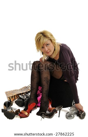 Full body view of lovely blond woman sitting on a pouf surrounded by lots of shopping bags and different shoes, trying on shoes, in elegant / business wear. Isolated on white background.