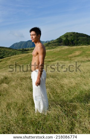 Full body Yong muscular man in sport standing on mountain