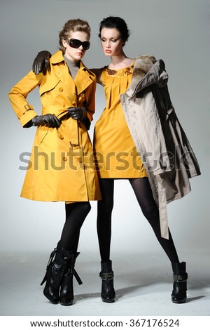 Full body young attractive two girl wearing sunglasses with yellow cloth posing  - stock photo