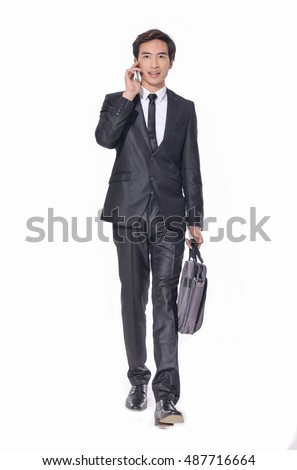 Full body young business man carrying a suitcase with mobile phone, Vertical shot.