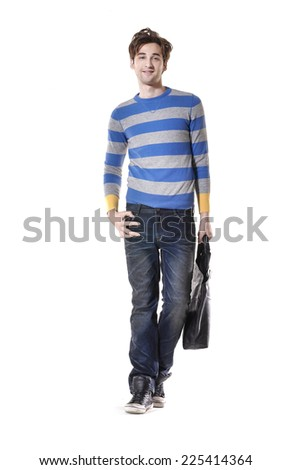 Full body young businessman standing with his bag walking in studio - stock photo