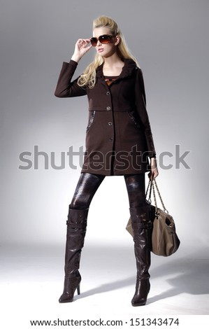 Full body young girl with long hair in sunglasses with bag over light background