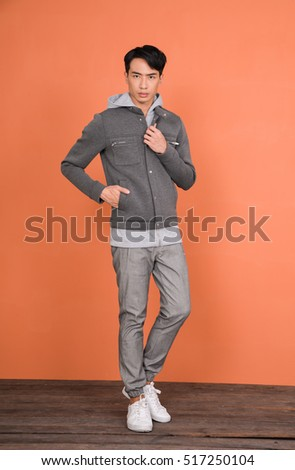 Full body young handsome man posing on wooden -orange background