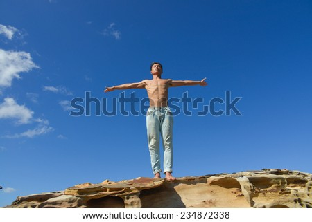 Full body young man doing yoga on sky background.
