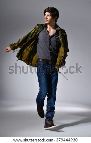 Full body young Man in Casual Clothes walking in light background - stock photo