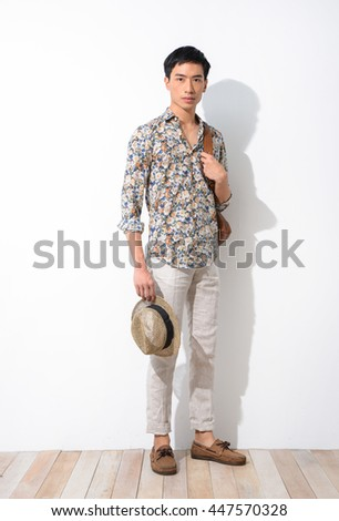 Full body young man with hat, bag standing on wooden board - stock photo