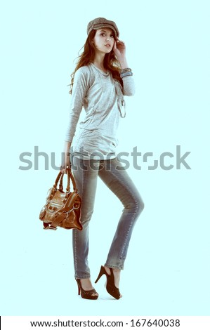 Full body young stylish brunette in a cap posing with bag-light blue background - stock photo