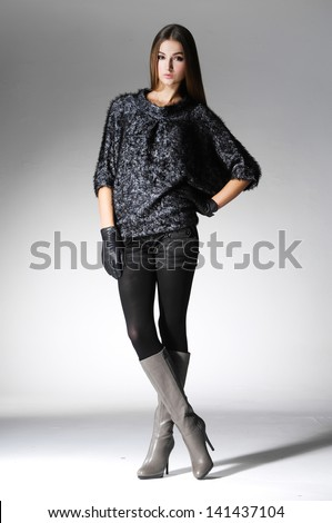 Full body young woman in fashion clothes posing over light background - stock photo