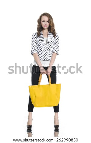 Full body young woman in yellow bag posing in studio - stock photo