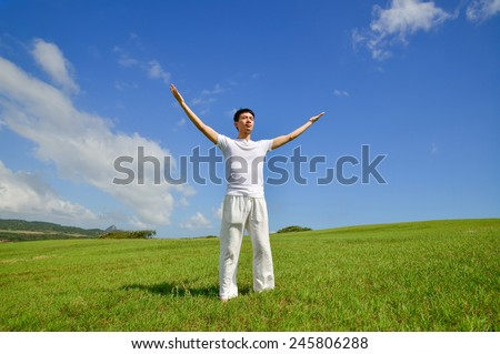 Full body young yoga man on field rising up his hands