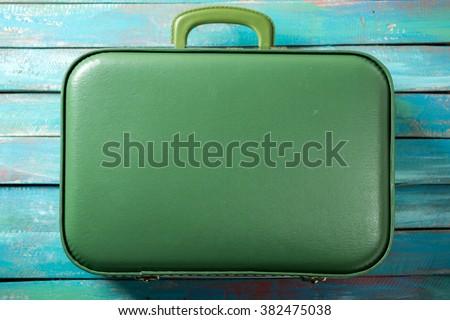 full boho suitcase on a distressed blue background - stock photo