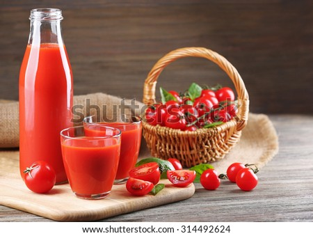 Full bottle and glasses of tomato juice with vegetables on wooden table close up - stock photo
