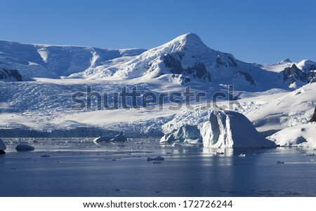 Full calm and reflection of icebergs in deep clear water. Travel by the research ship. Studying of colonies of penguins and weather in Antarctica. Snow and ices of the Antarctic islands.