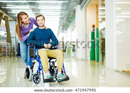 Full color image of young couple, handicapped man in wheelchair and his girlfriend, enjoying leisure time at shopping center together